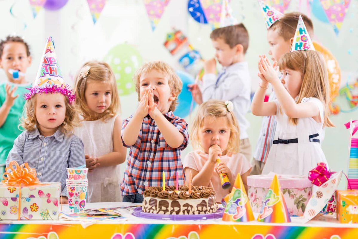 Gruppe von fröhlichen Kindern feiert einen Kindergeburtstag