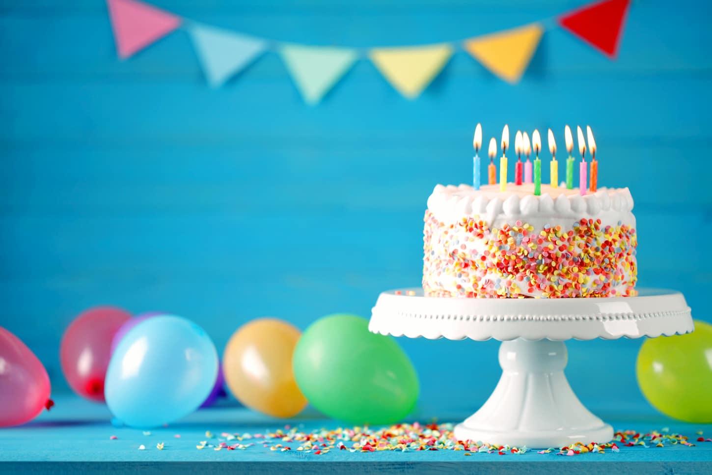 Farbenfroher Geburtstagskuchen mit Kerzen und Zuckerkonfetti